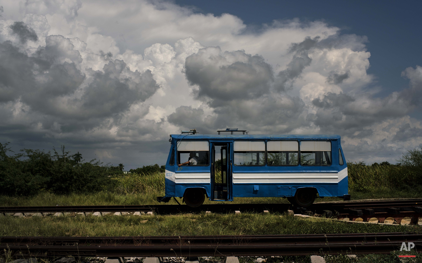 """In this Oct. 11, 2015 photo, a train wagon made to look like a bus, moves along the tracks on the outskirts of Trinidad, Cuba. This train, known as a """"train auto motor,"""" moves passengers to and from the outskirts of the city. (AP Photo/Ramon Espinosa)"""