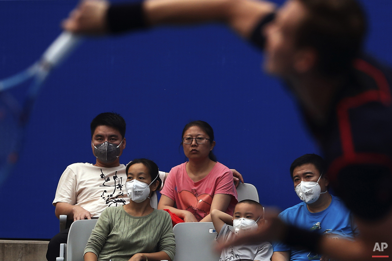 Spectators wearing masks to protect themselves from pollutants as they watch the men's singles match between Tomas Berdych of the Czech Republic and Pablo Cuevas of Uruguay in the China Open tennis tournament at the National Tennis Stadium in Beijing, Wednesday, Oct. 7, 2015. (AP Photo/Andy Wong)