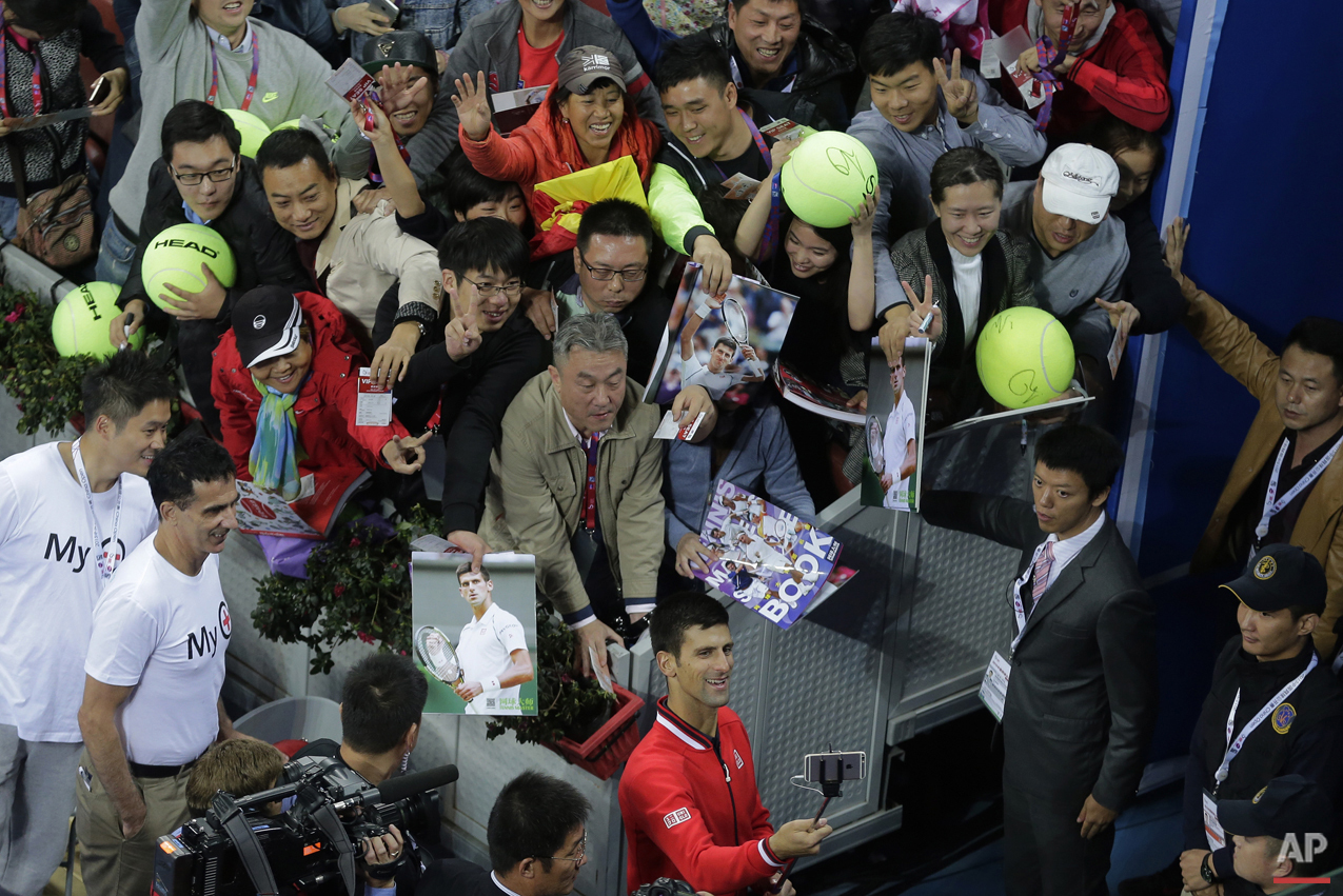 Novak Djokovic of Serbia, bottom, takes a selfie with spectators after winning his men's singles final match against Rafael Nadal of Spain in the China Open tennis tournament at the National Tennis Stadium in Beijing, Sunday, Oct. 11, 2015. (AP Photo/Andy Wong)
