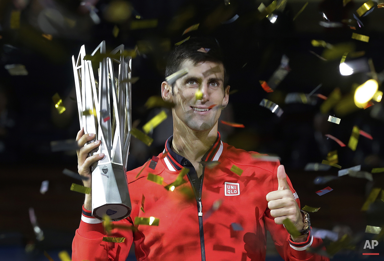 Novak Djokovic of Serbia gestures with his winner's trophy after he defeated Jo-Wilfried Tsonga of France in the final match of the Shanghai Masters tennis tournament at Qizhong Forest Sports City Tennis Center in Shanghai, China, Sunday, Oct. 18, 2015. (AP Photo/Andy Wong)