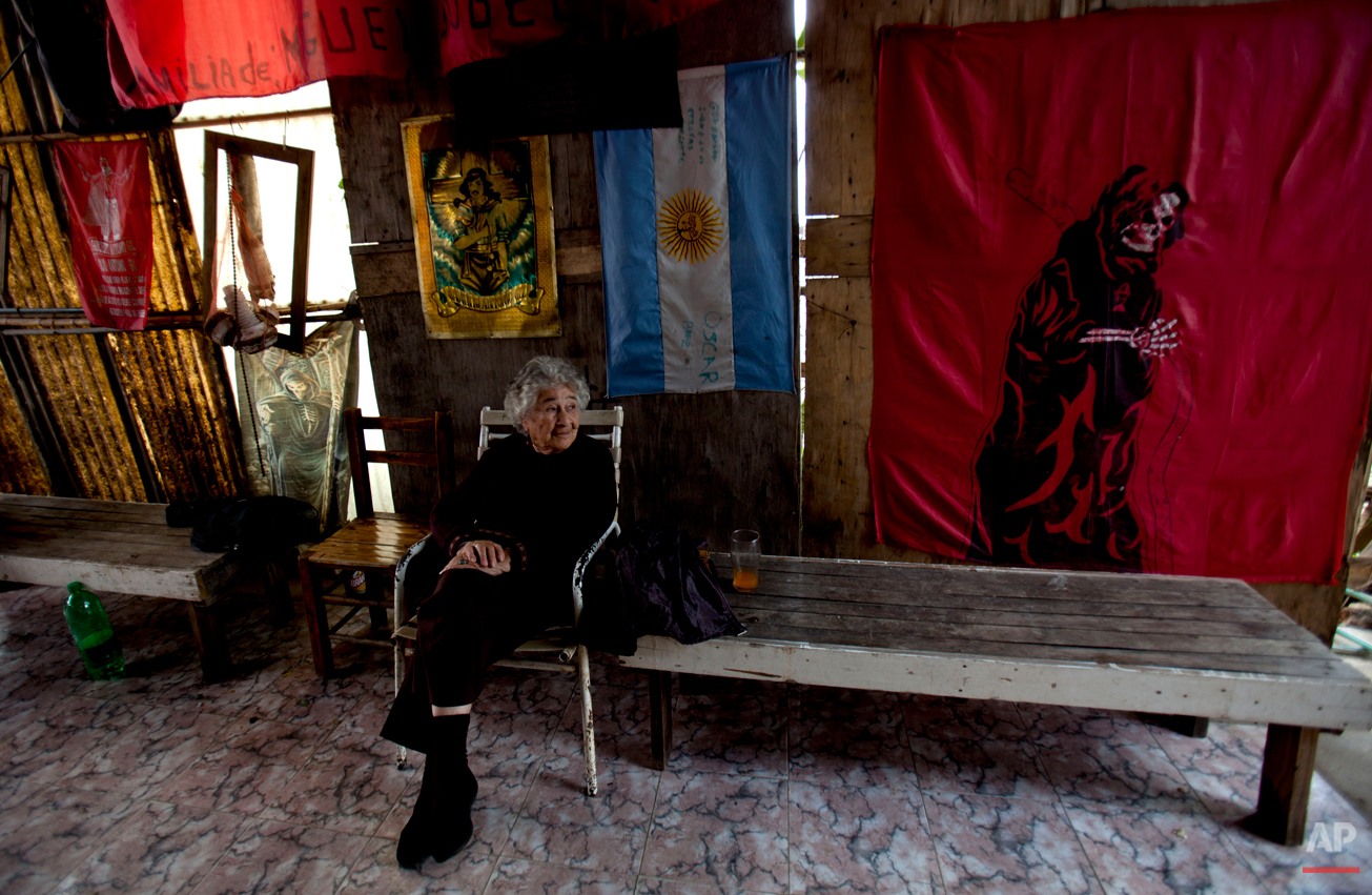 In this Oct. 8, 2014 photo, a woman sits inside a home decorated with images of San La Muerte, right, and Gauchito Gil, left, in the Carcova slum on the outskirts of Buenos Aires, Argentina. According to local legend, San La Muerte was a real-life man who died in prison helping lepers, and his body was found as a skeleton. Gil was a real man who was executed as an outlaw in 1878. Both are most popular characters among the lower economic class who pray to them for miracles. (AP Photo/Natacha Pisarenko)