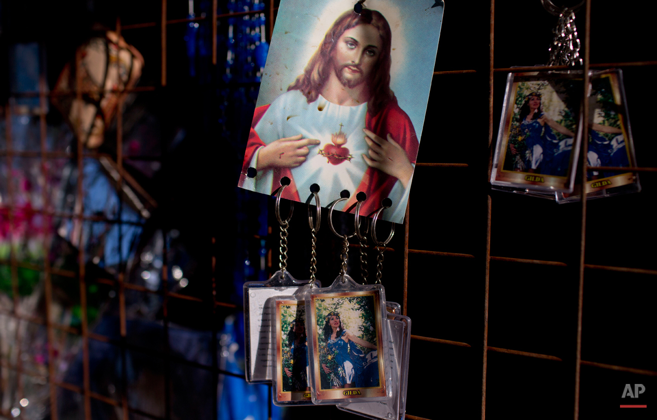 In this Sept. 7, 2014 photo, keychains of Argentina's late singer Gilda hang from a picture of Jesus Christ inside a sanctuary at the site where she died in a bus crash on the anniversary of her death in Entre Rios, Argentina. After the Argentine singer died at age 35 in a tragic road accident, her fans began attributing miracles to her, and gathering here on her birthday and the anniversary of her death to pray and thank her. (AP Photo/Natacha Pisarenko)