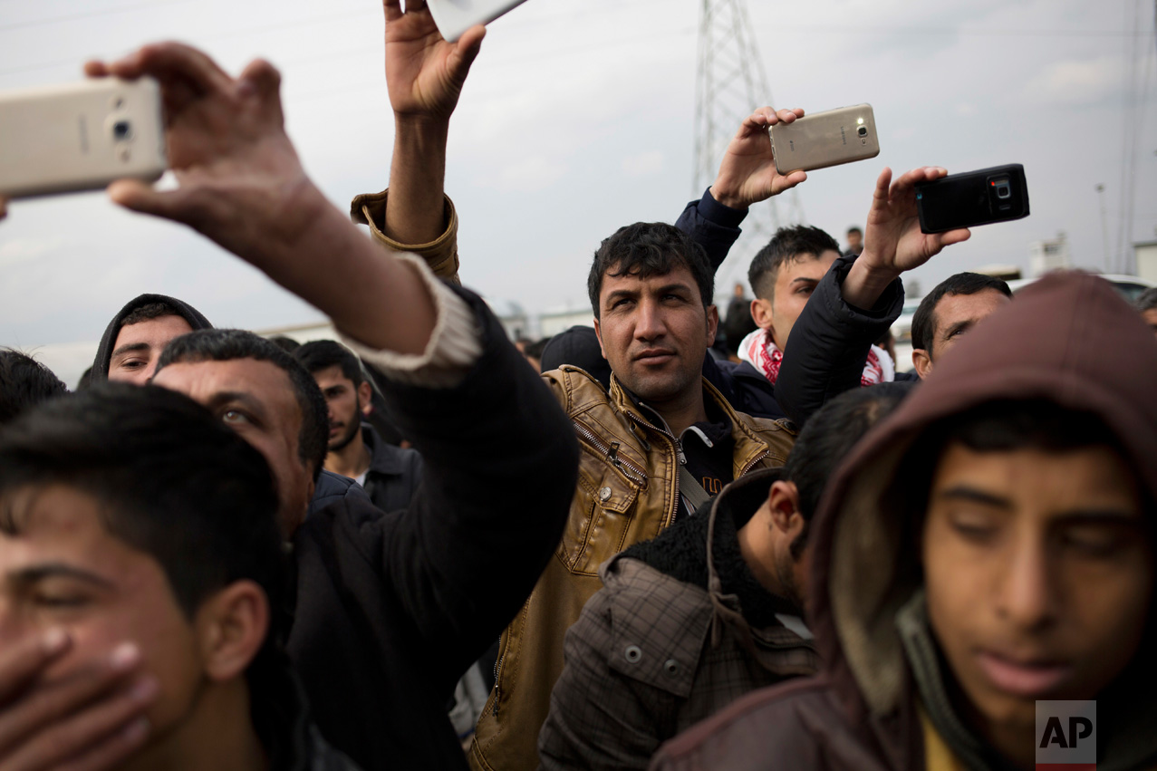 Displaced people from Mosul take photographs of a newlywed couple in the Khazer camp on Thursday, Feb. 16, 2017. It's the second marriage to take place in the IDP camps east of the city where tens of thousands are living, having fled the fighting in Mosul. (AP Photo/Bram Janssen)