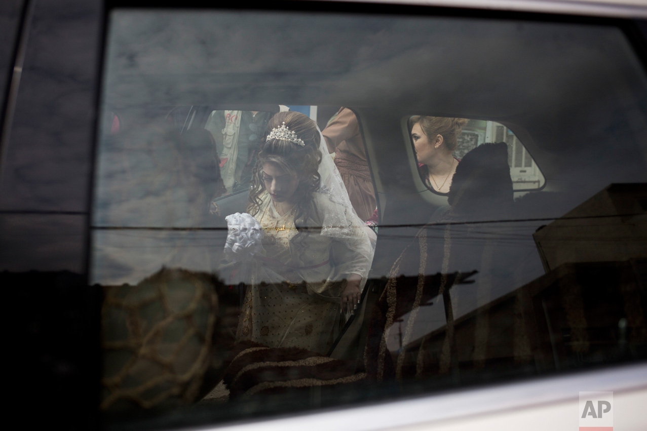 Shahad Ahmed Abed gets inside a car before driving to the Khazer camp for displaced people from Mosul where she was married on Thursday, Feb. 16, 2017. Abed and her 25-year-old husband Hussein Zeino Danoon fled from Mosul within the last month, just as Iraqi forces pushed Islamic State militants out of the eastern side of the city. (AP Photo/Bram Janssen)