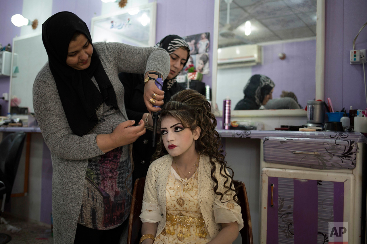 Shahad Ahmed Abed gets her hair done in a salon in Khazer for her wedding on Thursday, Feb. 16, 2017. Abed and her husband Hussein Zeino Danoon both fled from Mosul within the last month, just as Iraqi forces pushed Islamic State militants out of the eastern side of the city. (AP Photo/Bram Janssen)