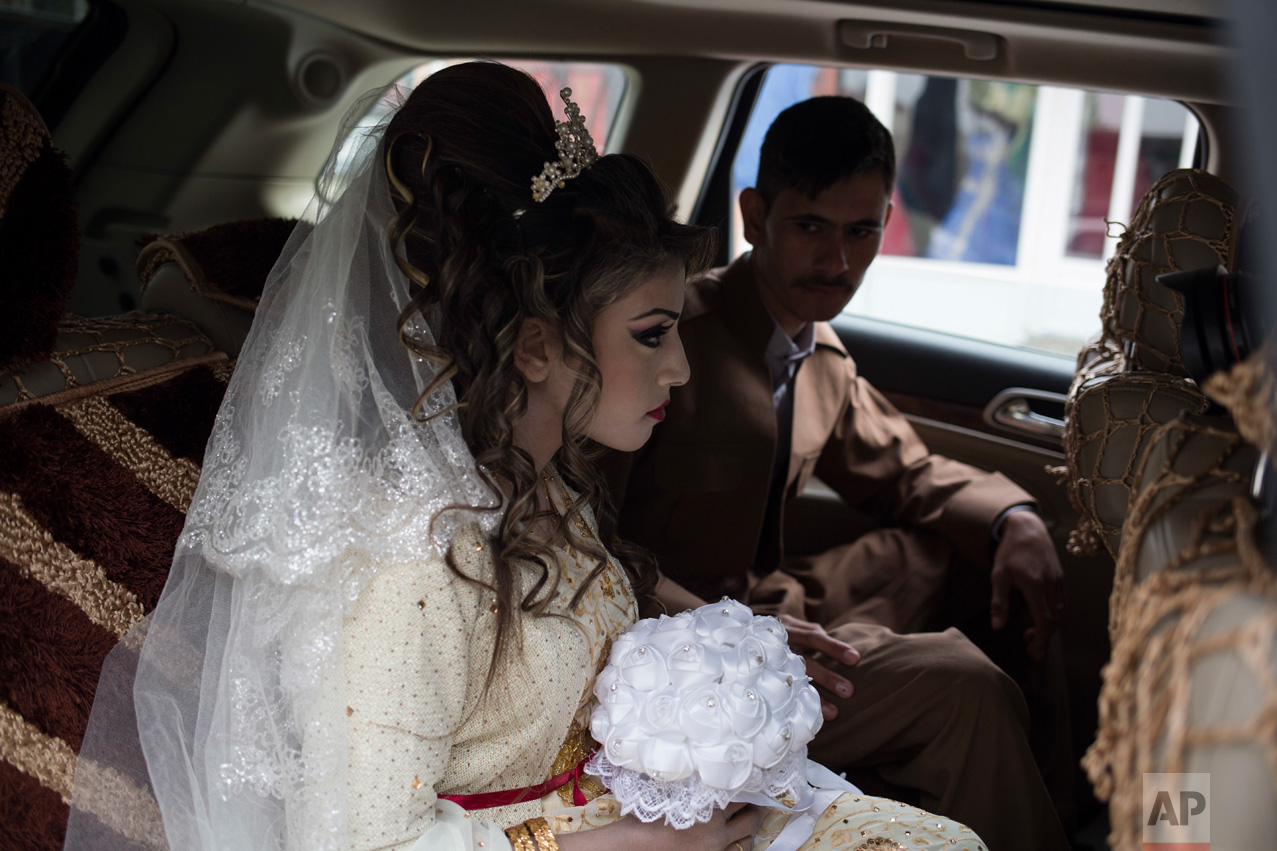 Hussein Zeino Danoon and Shahad Ahmed Abed sit inside a car before driving from the hair salon to the Khazer camp for their wedding near Mosul, Iraq, Thursday, Feb. 16, 2017. A bleak refugee camp in northern Iraq saw a rare outpouring of joy as the two celebrated their wedding less than a month after fleeing the fighting in Mosul. (AP Photo/Bram Janssen)