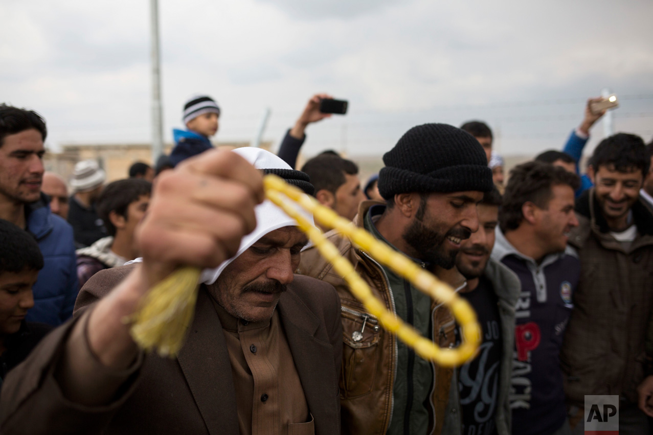 Displaced people from Mosul dance on traditional Kurdish music in the Khazer camp during a wedding on Thursday, Feb. 16, 2017. It's the second marriage to take place in the IDP camps east of the city where tens of thousands are living, having fled the fighting in Mosul. (AP Photo/Bram Janssen)