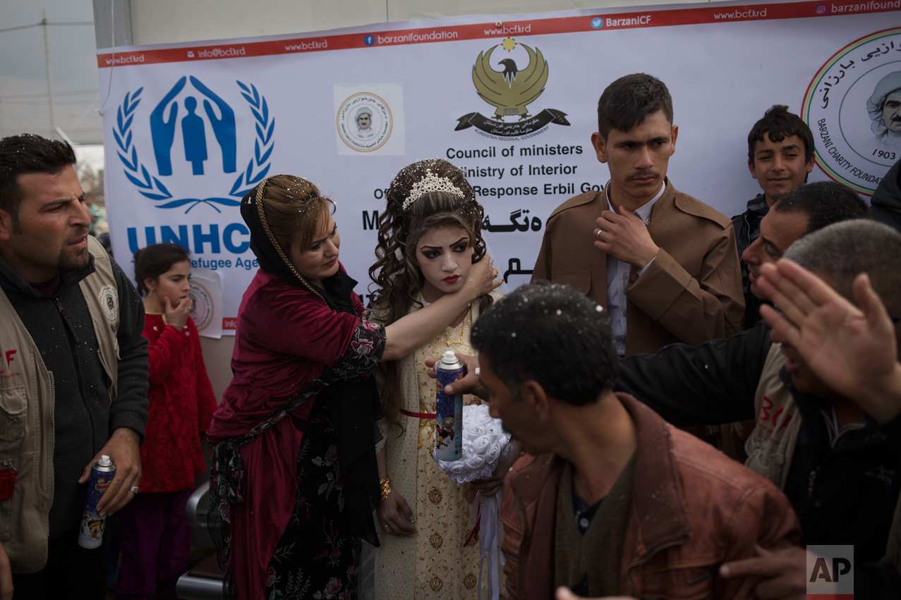 Hussein Zeino Danoon and Shahad Ahmed Abed are celebrated at their wedding in the Khazer camp for displaced people from Mosul, Thursday, Feb. 16, 2017. The wedding, organized and financed by the camp management, is the second marriage to take place in the IDP camps east of the city where tens of thousands are living, having fled the fighting in Mosul. (AP Photo/Bram Janssen)
