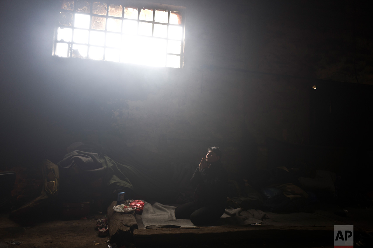 In this Friday, Feb. 3, 2017 photo, unaccompanied minor Caesar, 16, a migrant from Pakistan's tribal area of Bajaur, prays in an abandoned warehouse where he and other migrants took refuge in Belgrade, Serbia. (AP Photo/Muhammed Muheisen)