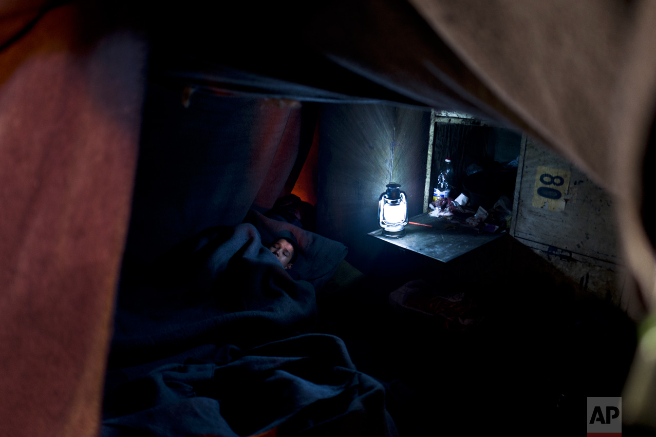 In this Wednesday, Feb. 15, 2017 photo, unaccompanied minor Liaqat, 12, a migrant from Khogyani, Afghanistan, sleeps on the ground inside a makeshift room made of blankets in an abandoned warehouse where he and other migrants took refuge in Belgrade, Serbia. (AP Photo/Muhammed Muheisen)