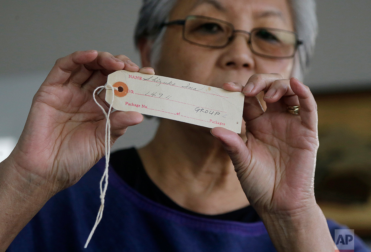 In this Feb. 10, 2017 photo, Satsuki Ina holds up an identification tag issued to her mother, Shizuko Ina, at her home in Oakland, Calif. As Japanese Americans mark the 75th anniversary of the executive order that authorized their incarceration, they're speaking out against new presidential orders that limit travel and target immigrants. (AP Photo/Jeff Chiu)