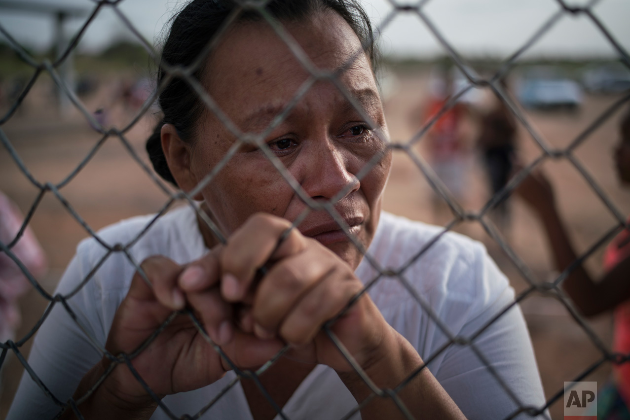 In this Feb. 2, 2017 photo, Katia Reis waits to deliver food to her son who's serving time at the Monte Cristo agricultural penitentiary in Boa Vista, Brazil. In this far northern city, at least 33 inmates were killed in a prison riot in January. (AP Photo/Felipe Dana)
