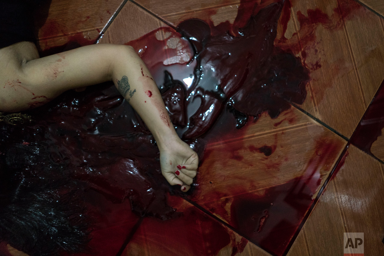 EDS. NOTE GRAPHIC CONTENT - In this Feb. 5, 2017 photo, the body of a woman who was shot to death under unclear circumstances lies in a pool of her own blood inside someone else's home in Manaus, Brazil. According to Claudio Lamachia, head of Brazil's bar association, Brazil's prisons are universities of crime, and from the inside, leaders give orders to commit crimes on the outside, including murder. (AP Photo/Felipe Dana)