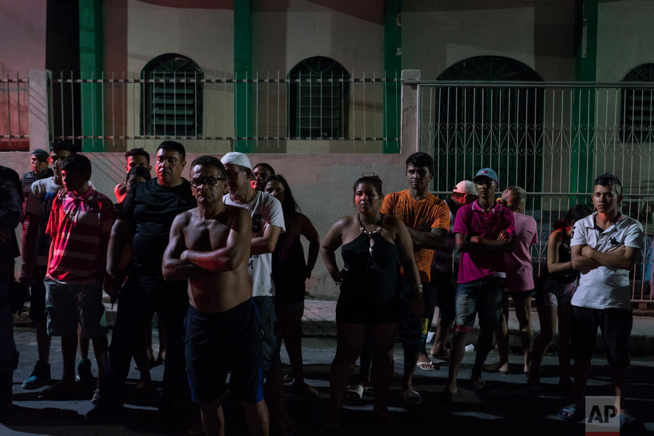In this Feb. 5, 2017 photo, residents watch police work at a crime scene where a man was murdered in Manaus, Brazil. The increasingly violent city is a thoroughfare for drug trafficking across South America, where authorities suspect most murders are gang related. (AP Photo/Felipe Dana)