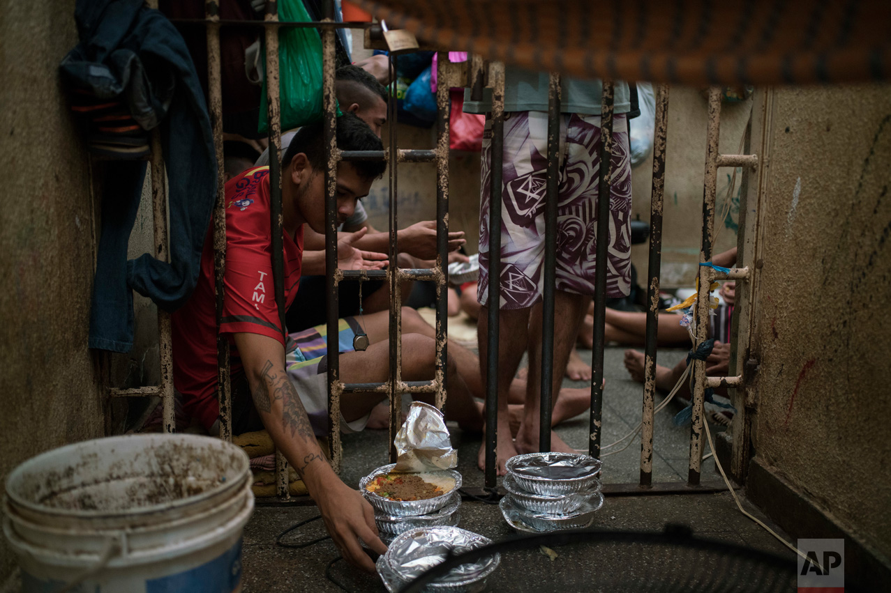 In this Feb. 6, 2017 photo, an inmate reaches for a plate of food during lunchtime inside an overcrowded cell at a police station near Manaus, Brazil. The business strategy of Brazilian crime gangs is to dominate overcrowded prisons, then control the streets. (AP Photo/Felipe Dana)In this Feb. 6, 2017 photo, an inmate reaches for a plate of food during lunchtime inside an overcrowded cell at a police station near Manaus, Brazil. The business strategy of Brazilian crime gangs is to dominate overcrowded prisons, then control the streets. (AP Photo/Felipe Dana)