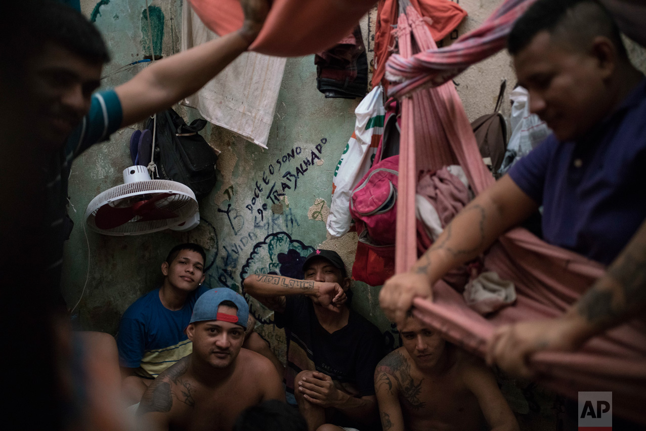 In this Feb. 6, 2017 photo, detainees sit inside an overcrowded cell at a police station near Manaus, Brazil. The walls are filled with infiltrations of moisture, the poor construction of the roof let almost no light shine inside and inmates put hammocks one on the top of the other, while one prisoner slept in the open bathroom. (AP Photo/Felipe Dana)