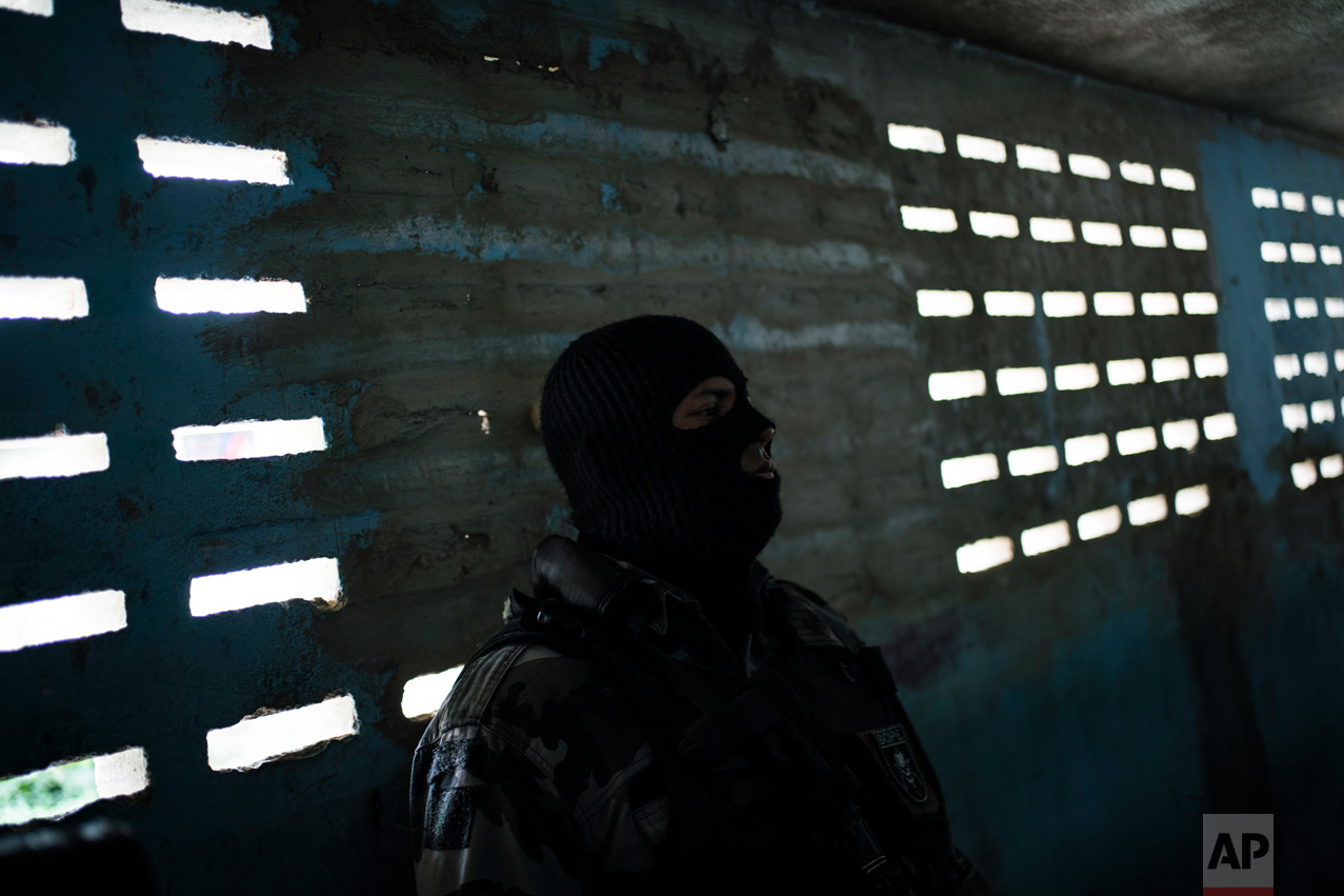 "In this Feb. 2, 2017 photo, a masked guard stands outside prison cells inside the Monte Cristo Agricultural Penitentiary in Boa Vista, Brazil. ""No one deserves to be here,"" a Venezuelan inmate here said through a small hole on the cell door. ""Not the good people, not the bad, not anyone."" (AP Photo/Felipe Dana)"