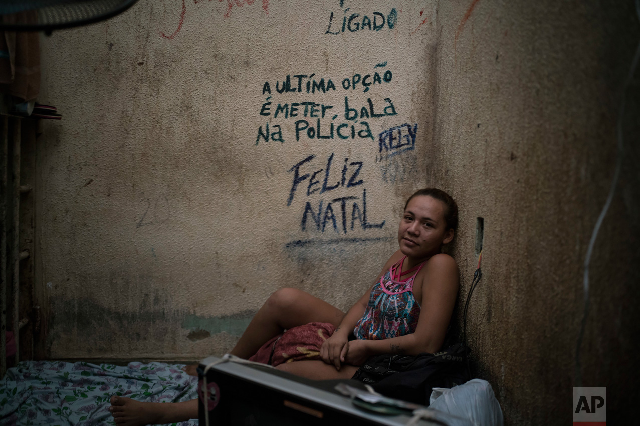 "In this Feb. 6, 2017 photo, female prisoner Regiane sits on her bed inside a corridor between two cells crowded with men at a police station near Manaus, Brazil. The message on the wall reads in Portuguese: ""The last option is to put a bullet in the police. Merry Christmas."" (AP Photo/Felipe Dana)"