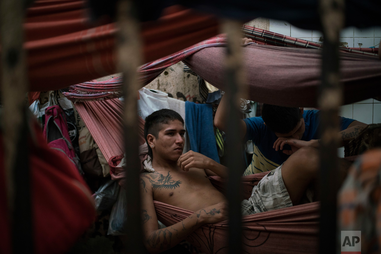 In this Feb. 6, 2017 photo, detainees rest in hammocks inside an overcrowded cell at a police station near Manaus, Brazil. All 24 inmates at the station said they were linked to the Family of the North gang, but guards said that could be just a defensive move after a slaughter at the city's main jail, Complexo Penitenciario Anisio Jobim. (AP Photo/Felipe Dana)