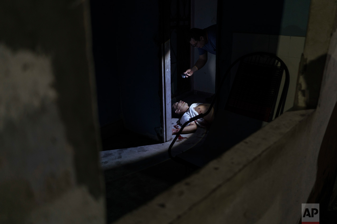 In this Feb. 5, 2017 photo, police inspect a murder victim on the floor of a home in Manaus, Brazil. The increasingly violent city is a thoroughfare for drug trafficking across South America, where authorities suspect most murders are gang related. (AP Photo/Felipe Dana)