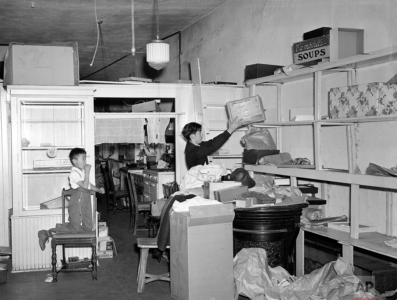"In preparation for the evacuation of Los Angeles' famed ""Little Tokyo"" section as a result of the ordering of 300,000 aliens and American-born Japanese from various Pacific coast combat zones, 20-year-old Yeichi Shoji, right, helps clear the shelves of the dry goods store operated by his parents, March 5, 1942, as Taro Sasai, 7, looks on. Shoji was born in the living quarters at the rear of the store, his elder brother is a soldier in the U.S. Army. (AP Photo/John T. Burns)"
