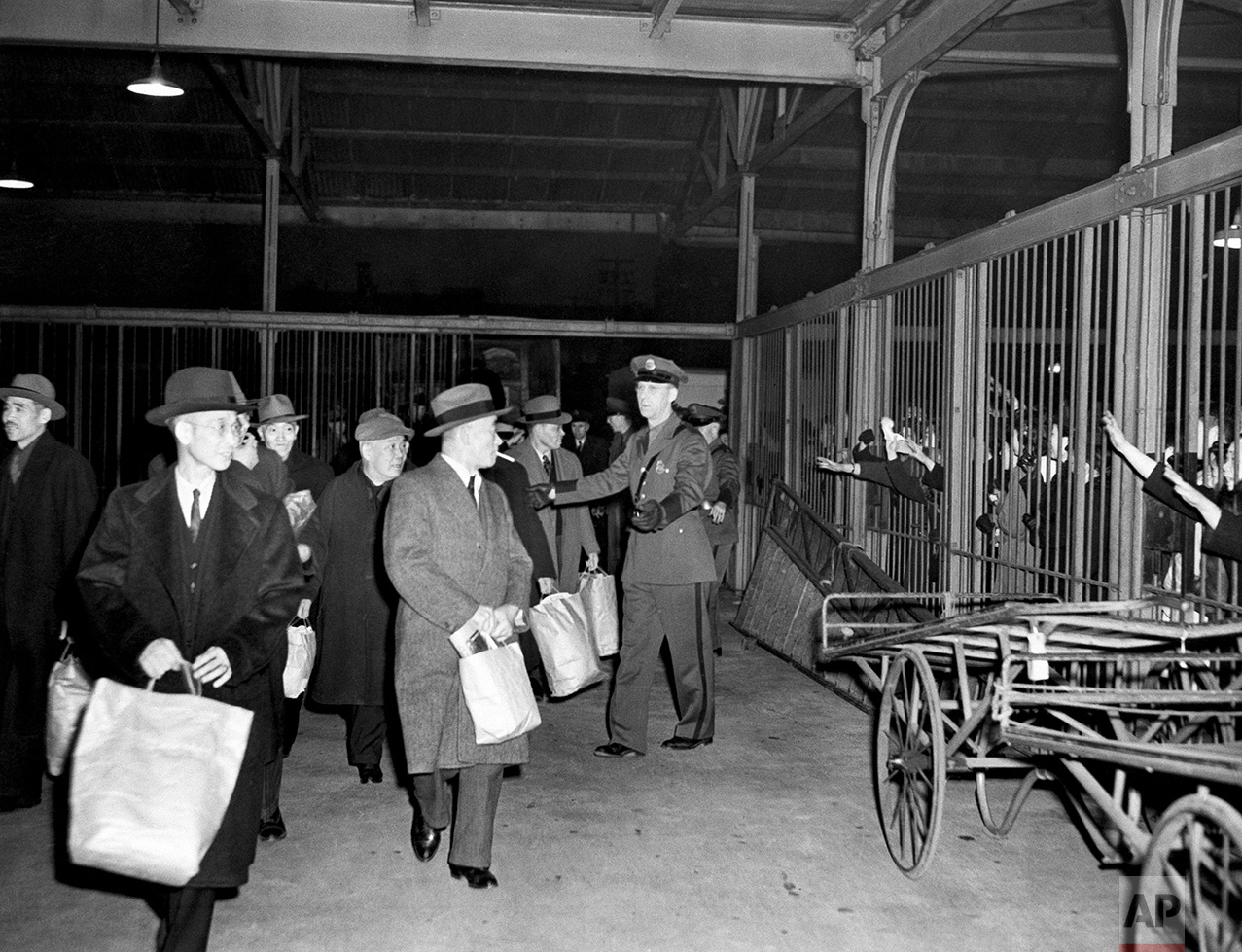 Interned Japanese, carrying belongings in paper bags, leave Seattle by train for Fort Missoula, Montana, March 19, 1942, while relatives waved through station cars, right. A group of 150 internees had been held in the Seattle immigration station. (AP Photo)