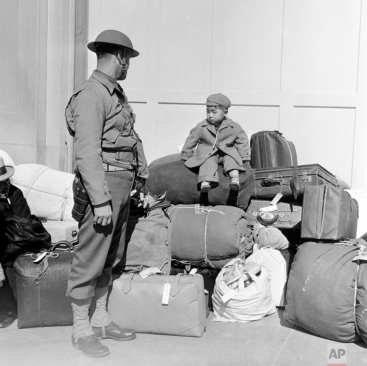 In this April 6, 1942 photo, a boy sits on a pile of baggage as he waits for his parents, as a military policeman watches in San Francisco. More than 650 citizens of Japanese ancestry were evacuated from their homes and sent to Santa Anita racetrack, an assembly center for war relocation of alien and American-born Japanese civilians. (AP Photo)