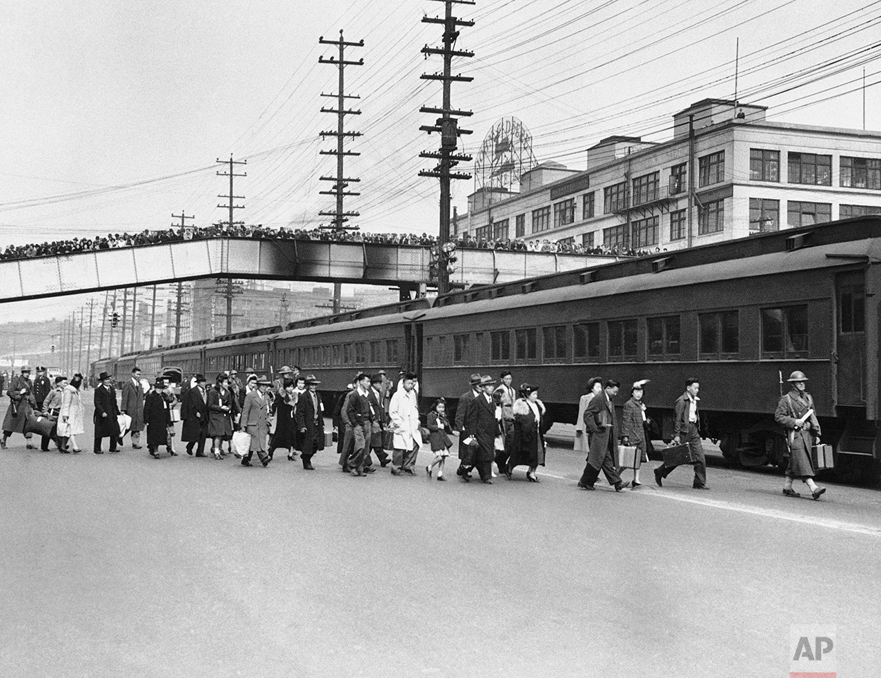 Seattle crowds jam an overhead walk to witness mass evacuation of Japanese from Bainbridge Island, Washington, March 30, 1942. Somewhat bewildered, but not protesting, some 225 Japanese men, women and children were taken by ferry, bus and train to California internment camps. Evacuation was carried out by the army. (AP Photo)