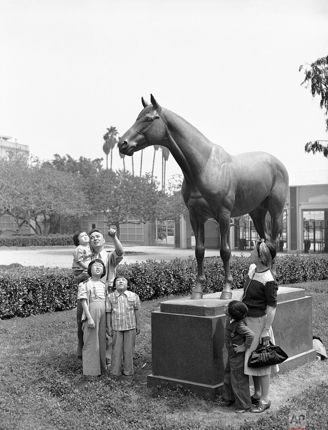 The statue of Seabiscuit, famous race horse, attracts members of an interned Japanese after they arrived at the Santa Anita race track in Arcadia, Calif., April 3, 1942. They were among the first group of evacuees to be quartered at the big racing plant which was converted into an assembly center for evacuated Japanese. (AP Photo/John T. Burns)