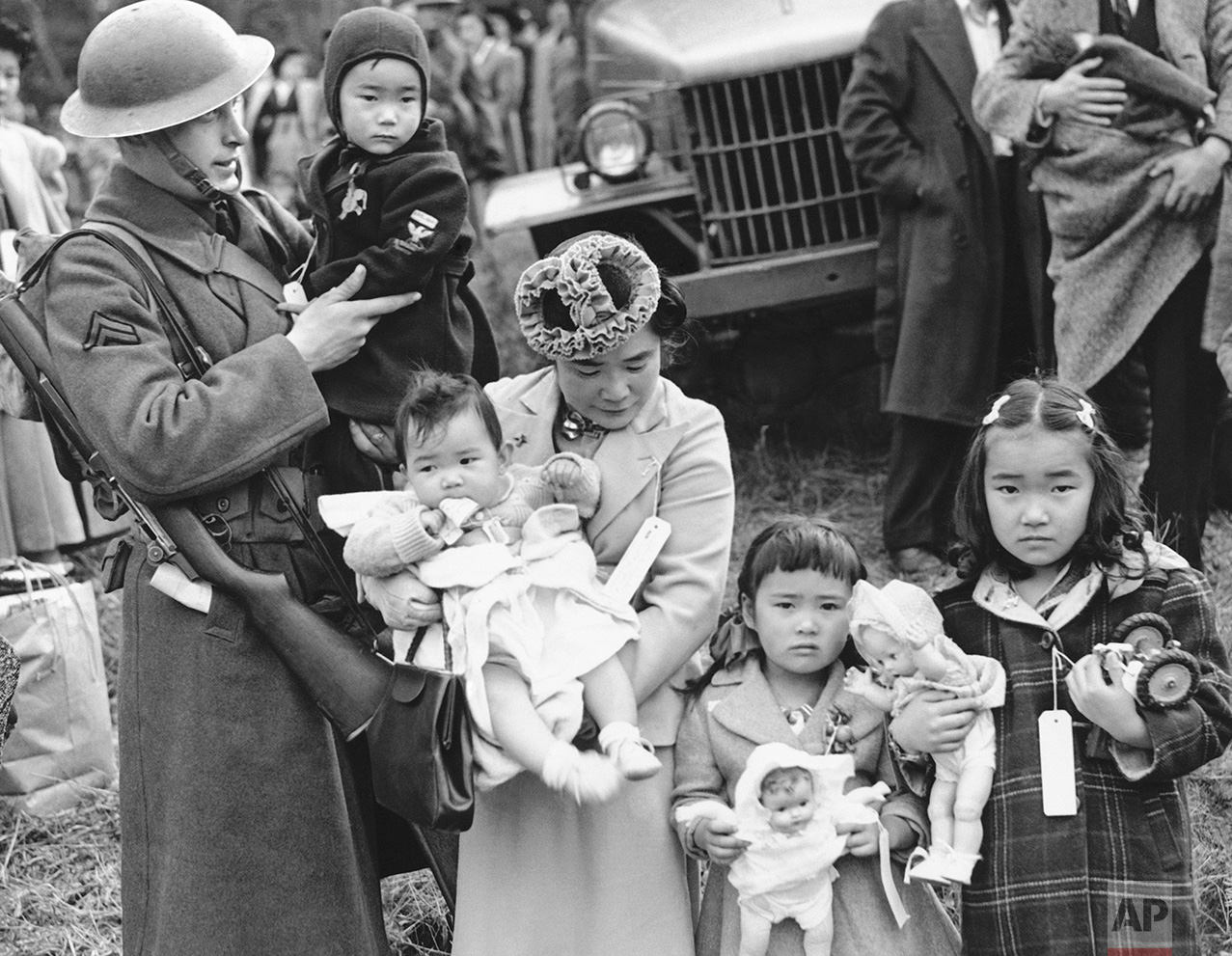 In this March 30, 1942 photo, Cpl. George Bushy, left, a member of the military guard which supervised the departure of 237 Japanese people for California, holds the youngest child of Shigeho Kitamoto, center, as she and her children are evacuated from Bainbridge Island, Wash. Roughly 120,000 Japanese immigrants and Japanese-Americans were sent to desolate camps that dotted the West because the government claimed they might plot against the U.S. (AP Photo)