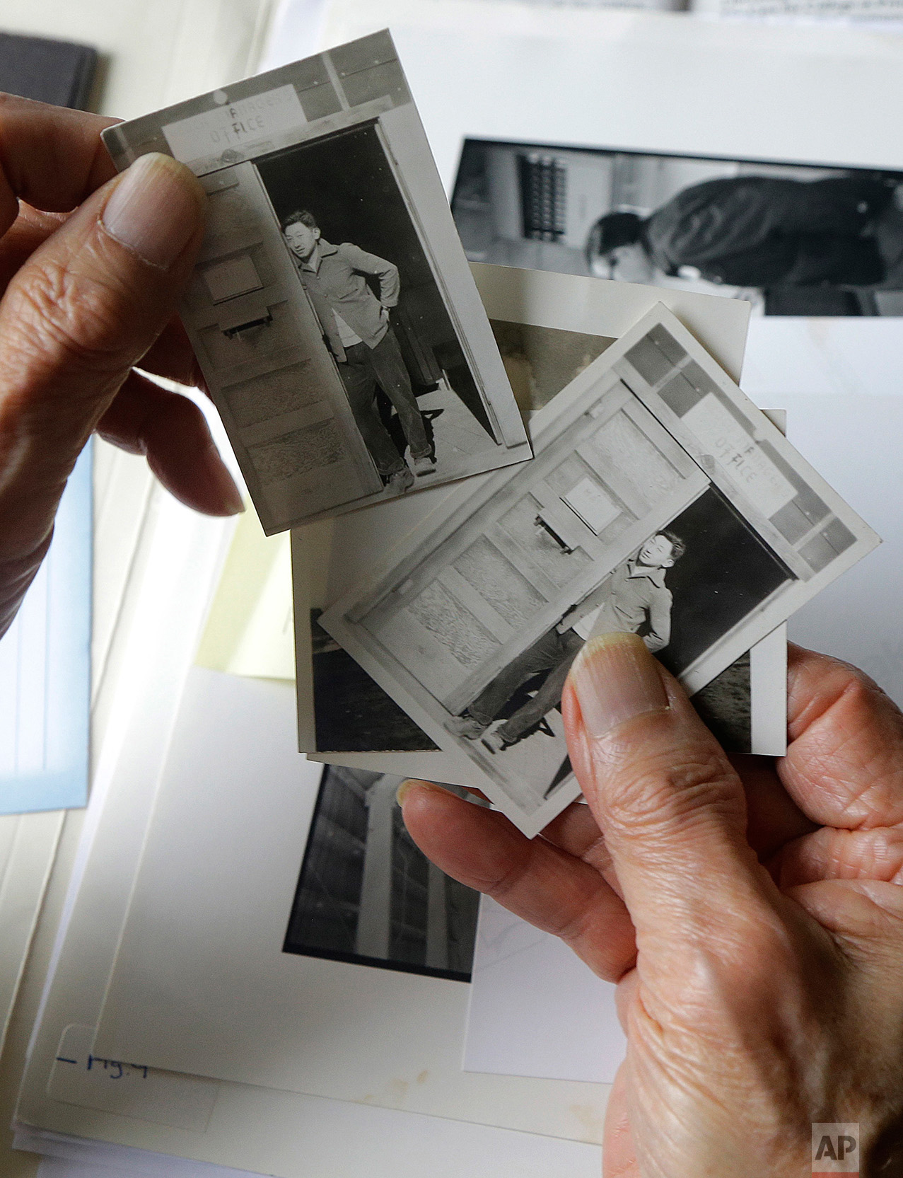 """In this Feb. 10, 2017 photo, Hiroshi Kashiwagi holds 1945 photos of himself at an internment camp in Tule Lake, Calif., at his home in San Francisco. Today, Kashiwagi, 94, is a poet and writer who speaks to the public about life at Tule Lake, a maximum security camp near the Oregon border. Winters were cold, the summers hot. They were helpless against dust storms that seeped inside. """"I feel obligated to speak out, although it's not a favorite subject,"""" he said. """"Who knows what can happen? The way this president is, he does not go by the rules. I'm hoping that he would be impeached."""" (AP Photo/Jeff Chiu)"""