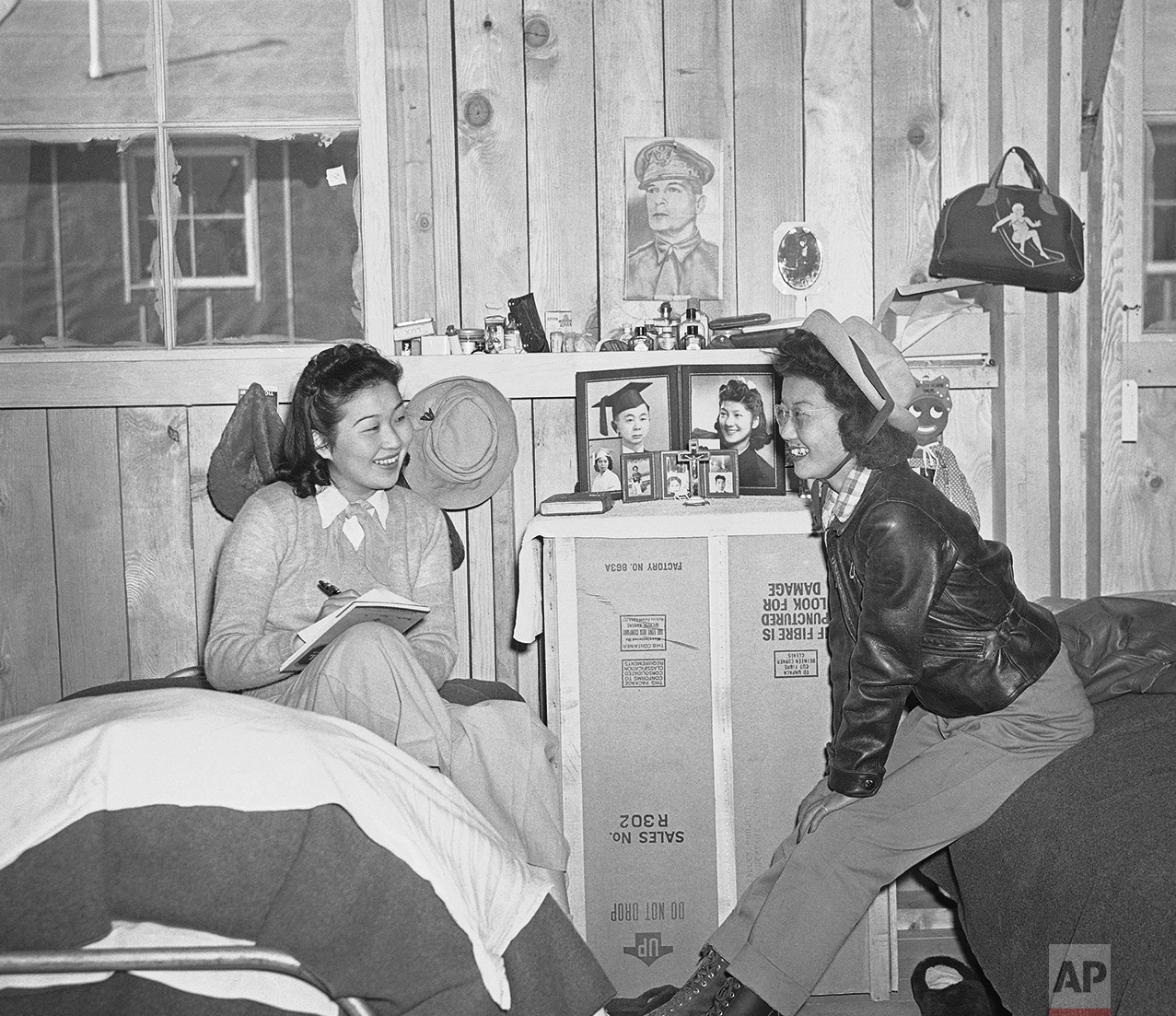 A picture of Gen. Douglas MacArthur, military nemesis of the Japanese forces, hung in a flace of honor, March 24, 1942 on the wall of the room of Gene Hashimoto (left) and Mary Wada was at the reception center established at Manzanar in the Owens Valley for Japanese evacuated from Los Angeles. Miss Hashimoto wrote friends at home of the new life at the hastily constructed community. (AP Photo)