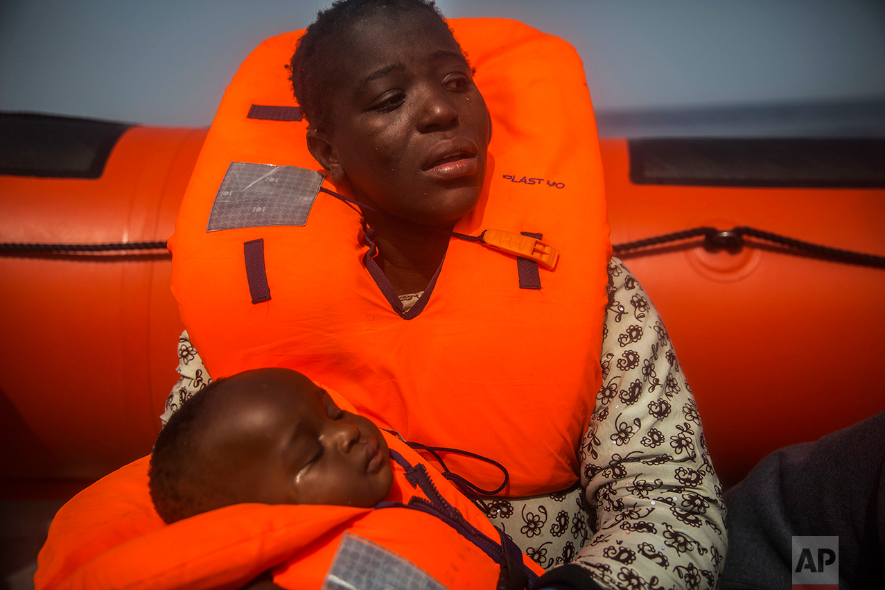 A woman from Ivory Coat holds her child, as they wait aboard a rubber boat out of control to be assisted by an NGO, 25 miles north of Sabratha, off the Libyan coast, early in the morning on Thursday, Feb. 23, 2017. (AP Photo/Santi Palacios)