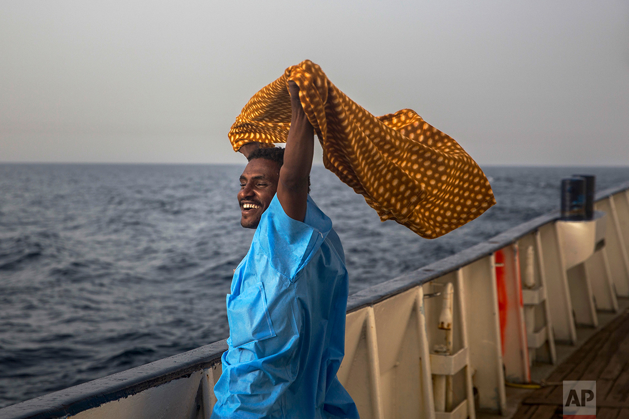 A man from Darfur, Sudan, celebrates to be rescued aboard Golfo Azzurro rescue ship, 25 miles north of Sabratha, off the Libyan coast, early in the morning on Thursday Feb. 23, 2017. (AP Photo/Santi Palacios)