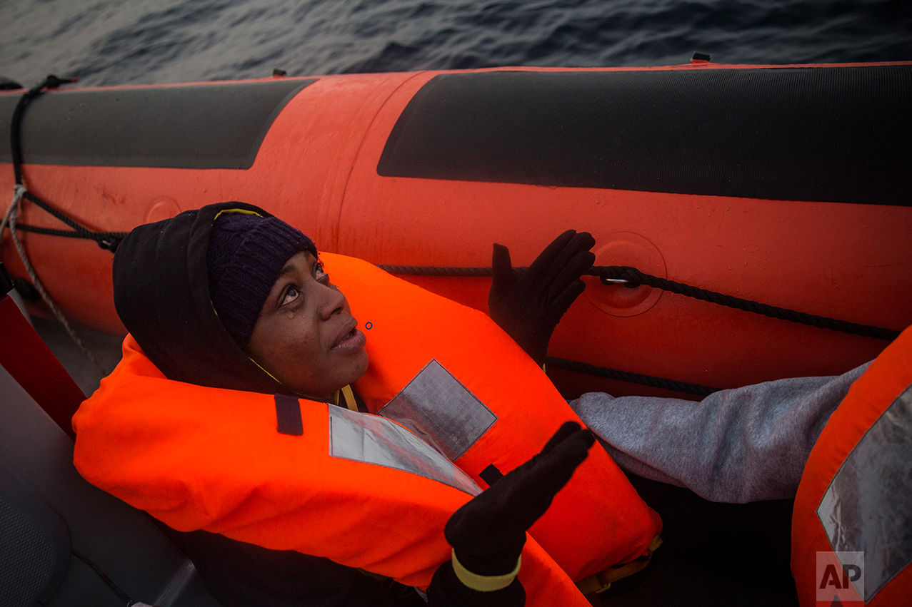 A Nigerian woman prays as she cries aboard a rescue boat, after being rescued by members of the Spanish NGO Proactiva Open Arms, when she was traveling with 98 other African refugees and migrants, mostly from Sudan and Senegal, aboard a rubber boat out of control at 25 miles north of Sabratha, off the Libyan coast, early in the morning on Thursday Feb. 23, 2017. (AP Photo/Santi Palacios)