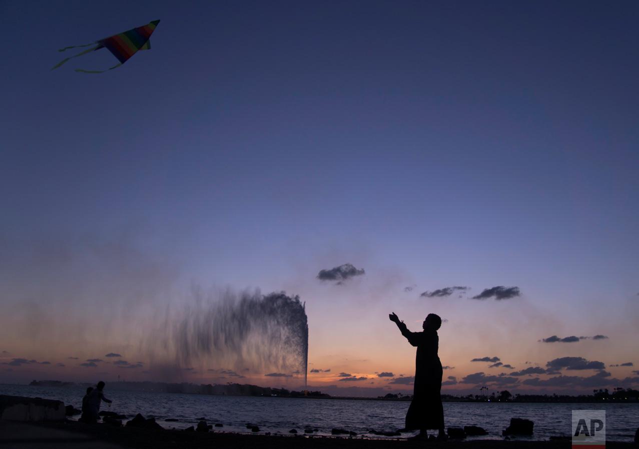 A boy flies a kite on the Red Sea beach near the landmark Jiddah fountain in Jiddah, Saudi Arabia, Monday, Feb. 20, 2017. (AP Photo/Amr Nabil)