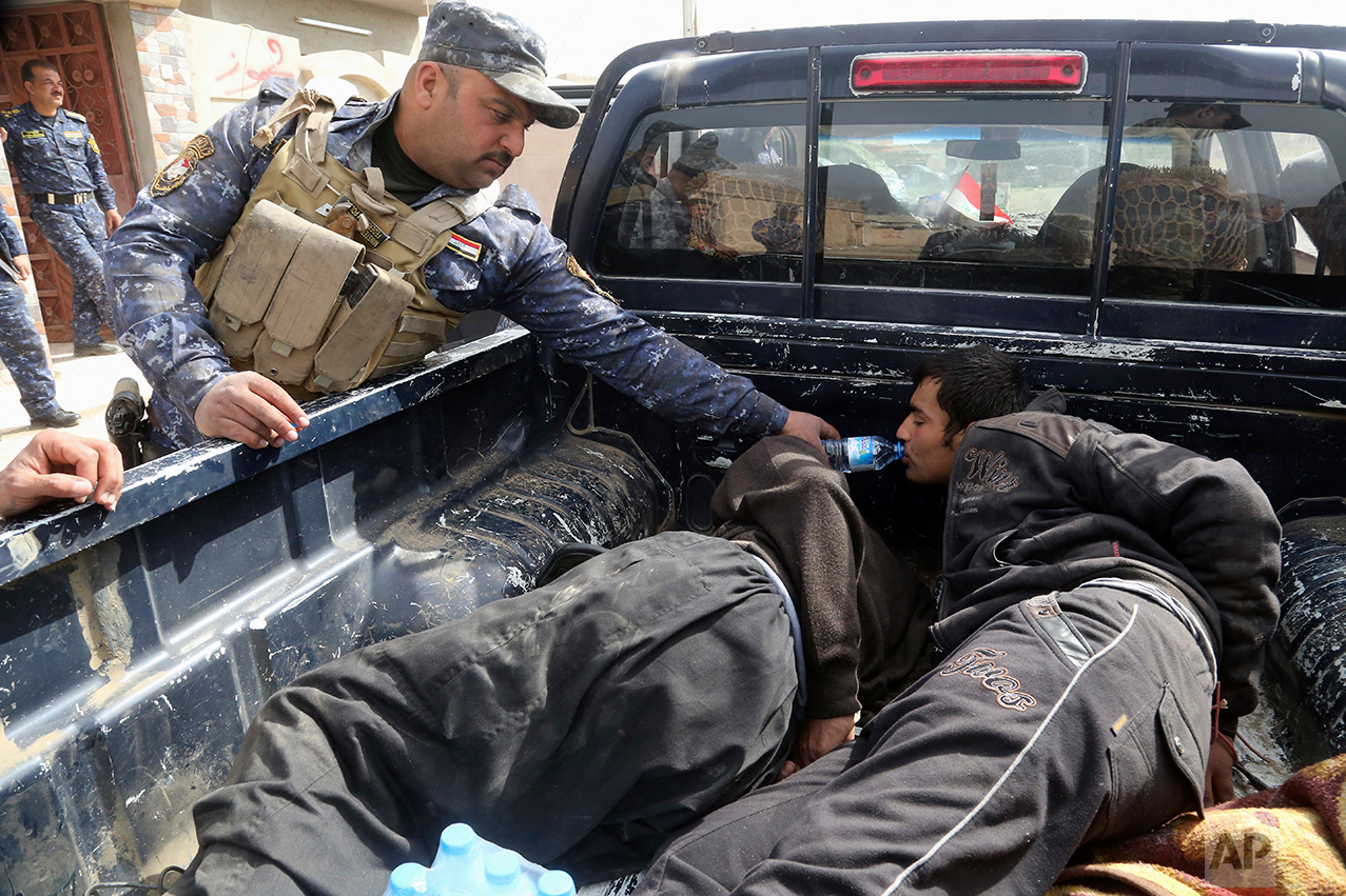 An Iraqi Federal policeman gives water to one of two handcuffed suspected Islamic State militants after they were arrested inside their home on the western side of Mosul, Iraq, Monday, Feb. 27. 2017. (AP Photo/Khalid Mohammed)