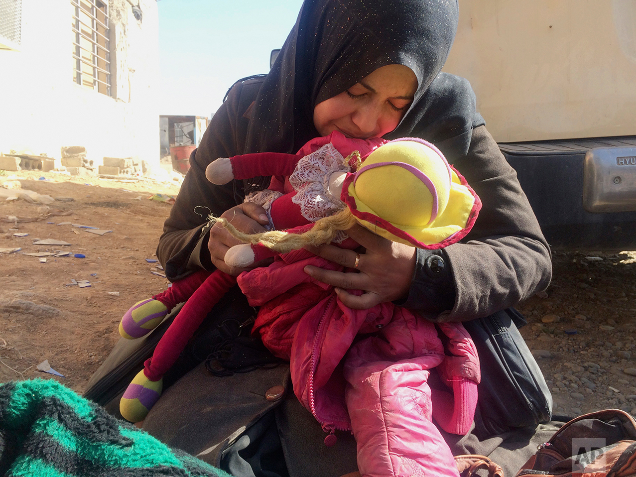Safana Hamad, a displaced Iraqi mother, holds her daughter  Manar's doll and jacket while mourning over her body, after the four-year-old was killed in an Islamic State mortar attack while trying to flee fighting between Iraqi security forces and Islamic State militants, in western Mosul, Iraq on Sunday, Feb. 26, 2027. (AP Photo/Susannah George)