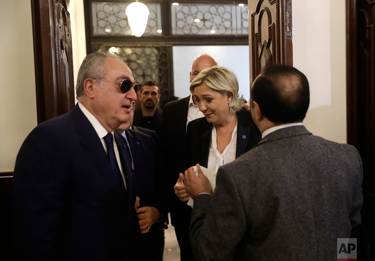 An aide of Lebanon's Grand Mufti Sheikh Abdel-Latif Derian, right, holds a head scarf as he tries to convince French far-right presidential candidate Marine Le Pen, center, to wear it during her meeting with the Mufti but she refused, at Dar al-Fatwa the headquarters of the Sunni Mufti, in Beirut, Lebanon, Tuesday, Feb. 21, 2017. Le Pen refused to go into a meeting with Lebanon's Grand mufti after his aides asked her to wear a head scarf. Le Pen said she met in the past with the Grand mufti of Egypt's Al-Azhar, one of the world's top Sunni clerics, without wearing a veil. Once she was told it is different here, Le Pen walked toward her car and left. (AP Photo/Hussein Malla)