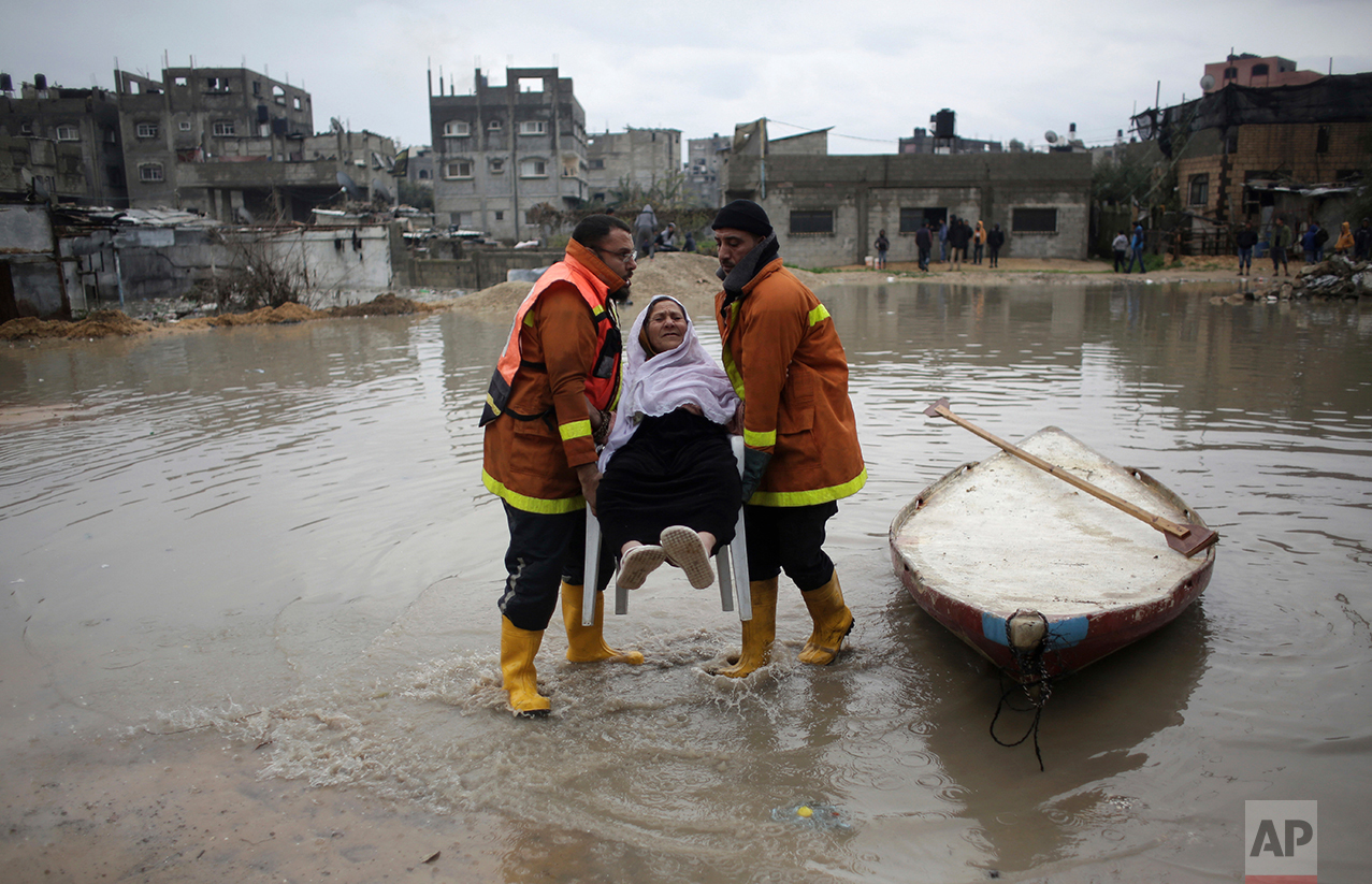 Palestinian rescue members evacuate a woman from her flooded home during a heavy rain storm in Jabaliya refugee camp, northern Gaza Strip, Thursday, Feb. 16, 2017 (AP Photo/ Khalil Hamra)