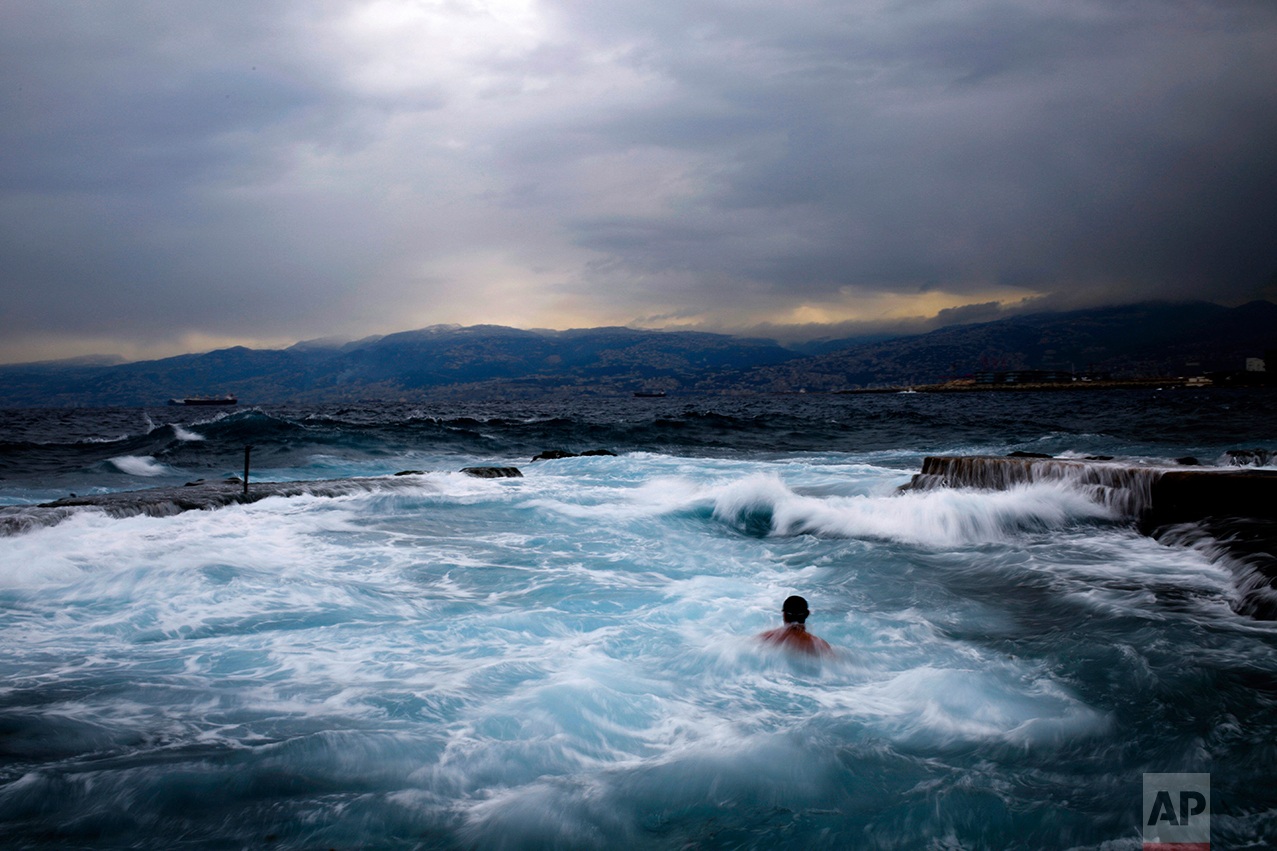 Men swim during in the early morning in the Mediterranean sea in cool temperatures of 8 degrees celsius, 46.4 Fahrenheit, across Beirut, Lebanon, Thursday, Feb. 16, 2017. (AP Photo/Hassan Ammar)