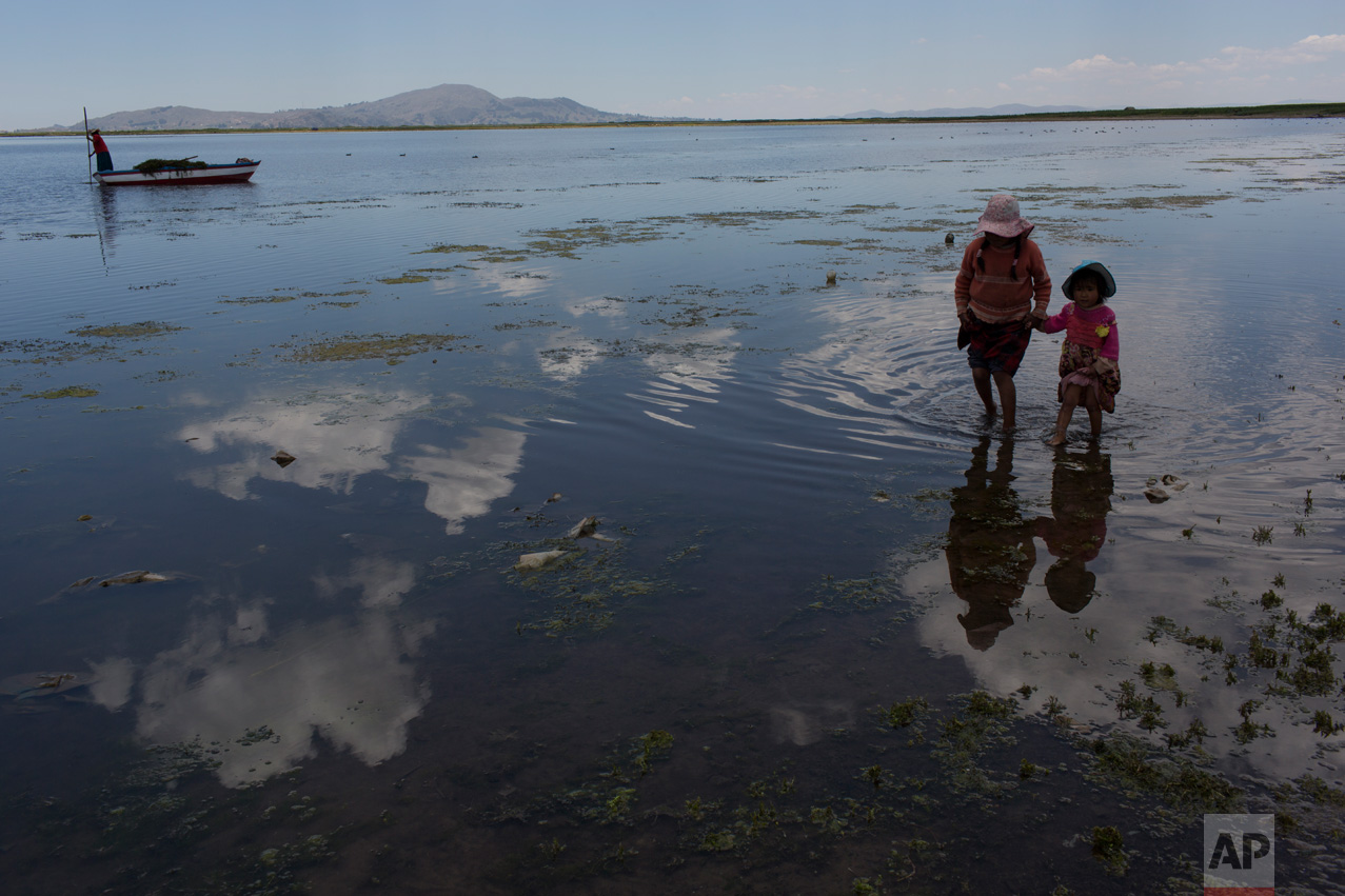 In this Feb. 2, 2017 photo, cousins from the Avila family search for discarded toys on the shores of Lake Titicaca, in Coata in the Puno region of Peru. The shores of South America's largest lake are littered with dead frogs, discarded paint buckets and bags of soggy trash. Less visible threats lurk in the water itself: highly toxic levels of lead and mercury. (AP Photo/Rodrigo Abd)