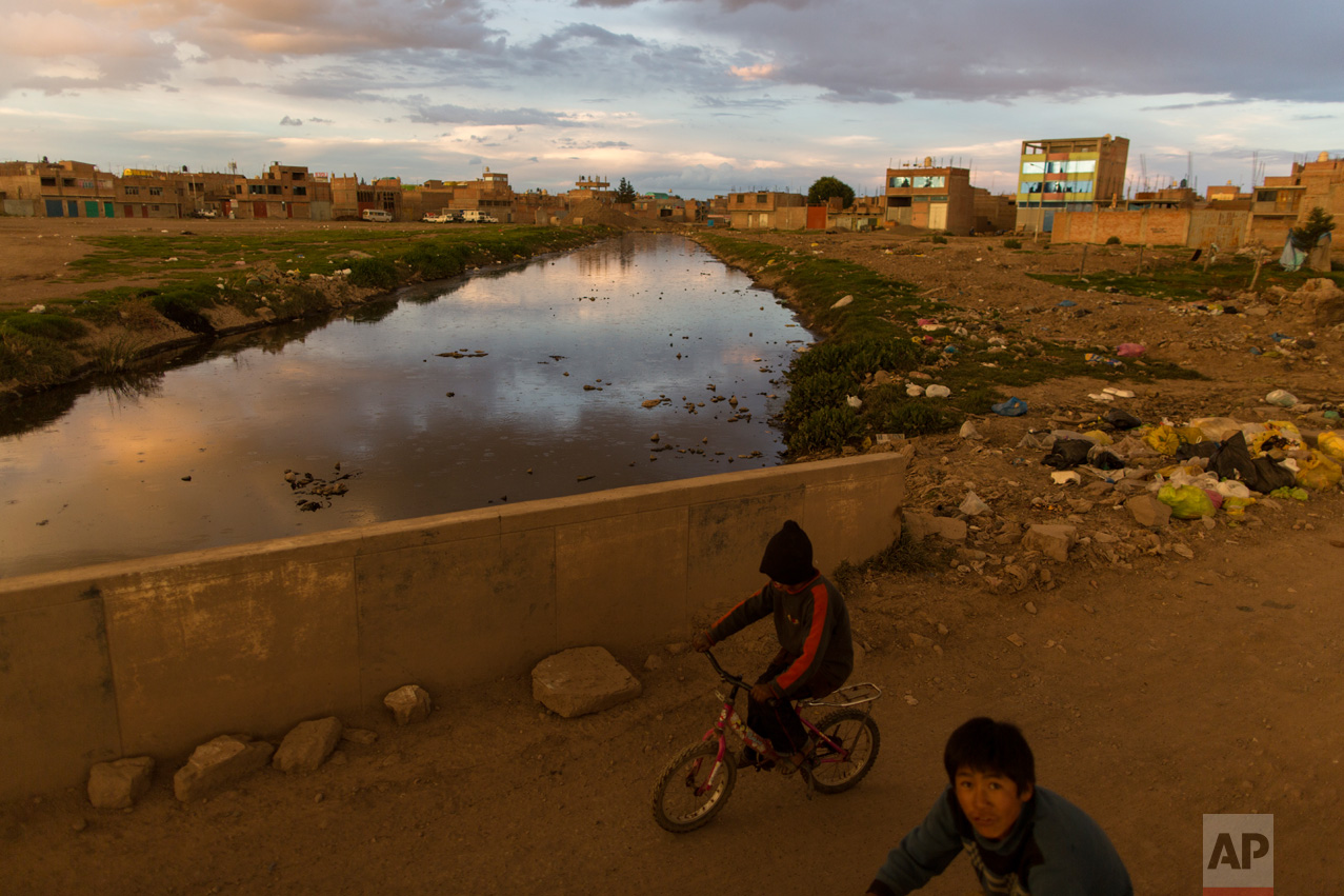In this Feb. 1, 2017 photo, children ride bikes along the Torococha River near a municipal waste treatment plant with water that flows into Lake Titicaca, in Juliaca, in the Puno region of Peru. Many of the more than 400,000 tourists who visit Lake Titicaca from Peru each year stop first in Juliaca, a town that produces 200 tons of trash daily, much of it winding up in a river that has turned into a conveyor belt of waste heading into the lake. (AP Photo/Rodrigo Abd)
