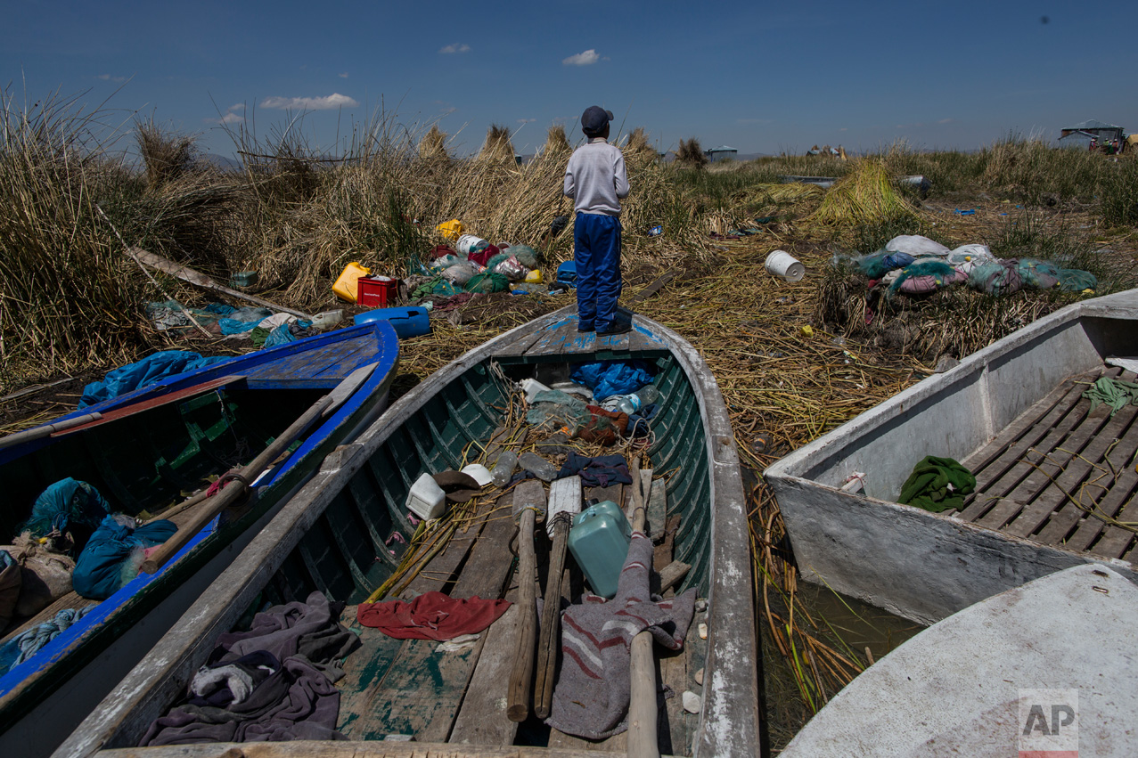 """In this Feb. 2, 2017 photo, a boy stands on a fishing boat on the littered shore of Lake Titicaca in Kapi Cruz Grande, in the Puno region of Peru. The camouflage-colored Titicaca water frogs that used to be in abundance have thinned in numbers and have been placed on a """"critically endangered"""" list by the International Union for Conservation of Nature and just 10,000 remain. (AP Photo/Rodrigo Abd)"""