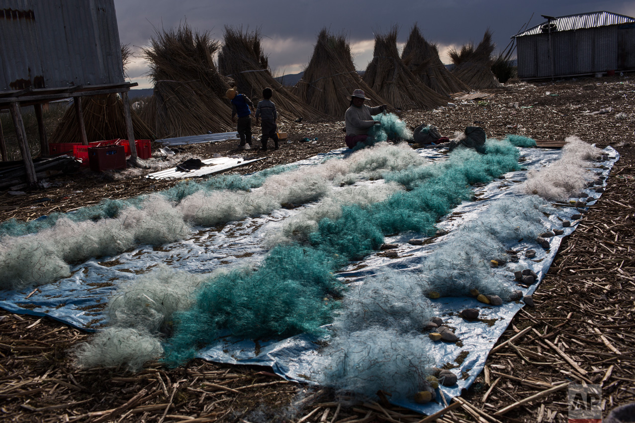 In this Feb. 4, 2017 photo, Naty Lugano Quispe cleans fish nets in Kapi Cruz Grande, a village on the shore of Lake Titicaca, in the Puno region of Peru. A 2014 study suggested officials limit some fish consumption, but area inhabitants said they weren't informed about the study or told they could be consuming fish containing mercury, cadmium, zinc and copper at levels higher than those advised for human consumption. (AP Photo/Rodrigo Abd)