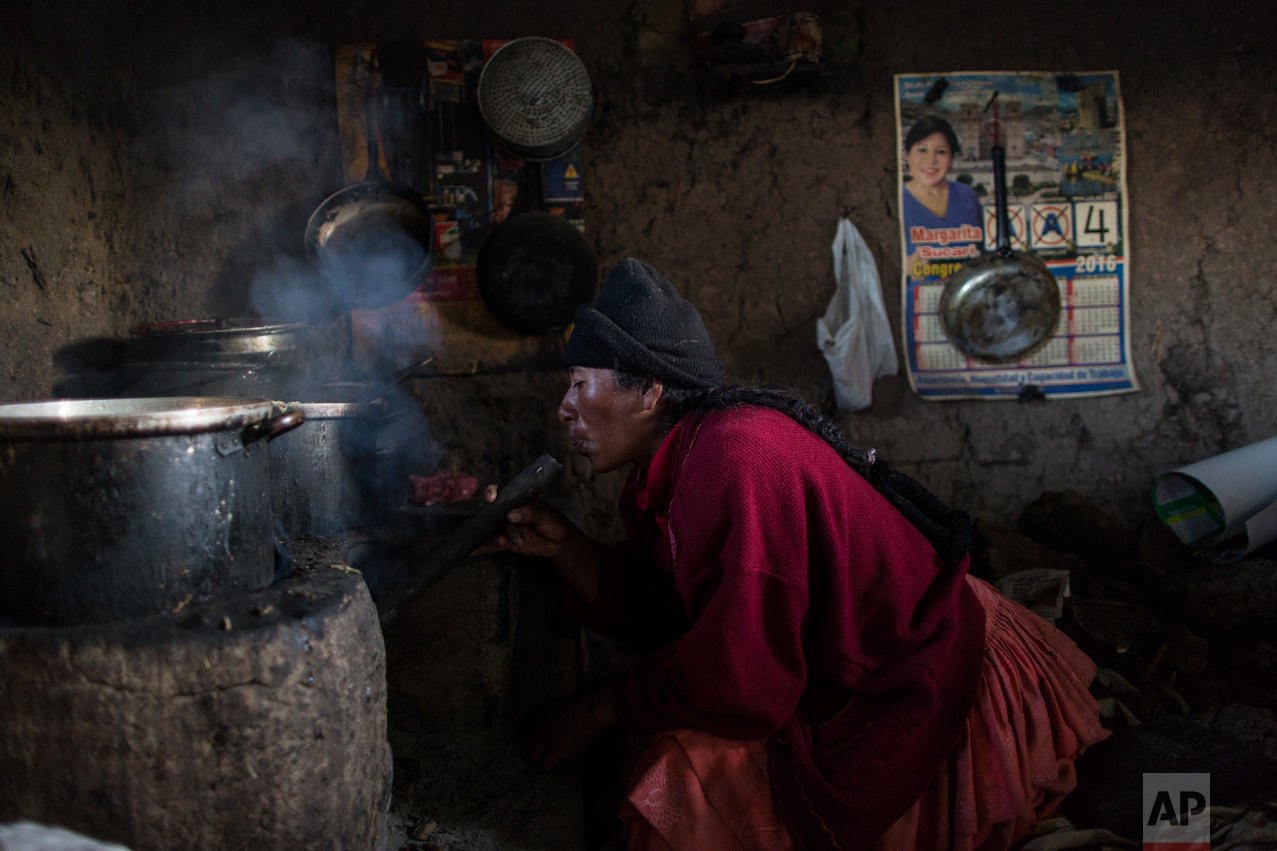 """In this Feb. 4, 2017 photo, Lilian Avila Diaz lights her firewood stove to cook lunch for her family in Coata, a small village on the shore of Lake Titicaca, in the Puno region of Peru. The amount of mercury consumed by Titicaca residents is """"unacceptable,"""" according to Dr. Jane M. Hightower, who specializes in internal medicine at the California Pacific Medical Center in San Francisco and author of the book """"Diagnosis: Mercury: Money, Politics & Poison,"""" after reviewing a 2014 study on fish caught from Lake Titicaca. (AP Photo/Rodrigo Abd)"""