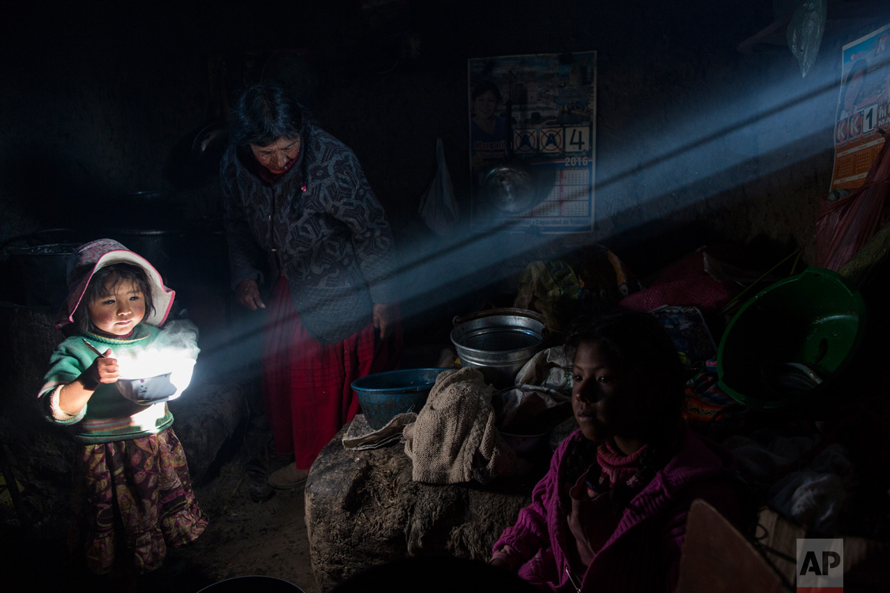 In this Feb. 4, 2017 photo, a child holds a bowl of hot food as the Avila family has lunch at their home in Coata, a small village on the shore of Lake Titicaca in the Puno region of Peru. Lake Titicaca was once worshipped by Incas who proclaimed its deep blue waters the birthplace of the sun, but today high levels of mercury, cadmium, zinc and copper are found in the fish locals consume, according to a 2014 government study. (AP Photo/Rodrigo Abd)