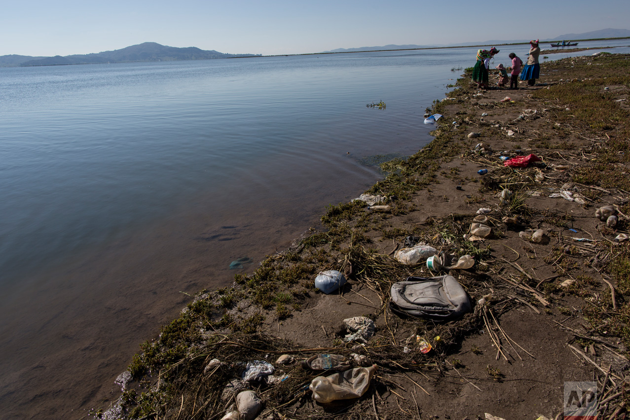"""In this Feb. 3, 2017 photo, trash covers the shores of Lake Titicaca where environmental activist Maruja Inquilla talks to locals in Coata, in the Puno region of Peru. Inquillla is alerting neighboring villagers of the dangers lurking in their food and water. """"If the frogs could talk they would say, 'This is killing me,'"""" she said. (AP Photo/Rodrigo Abd)"""