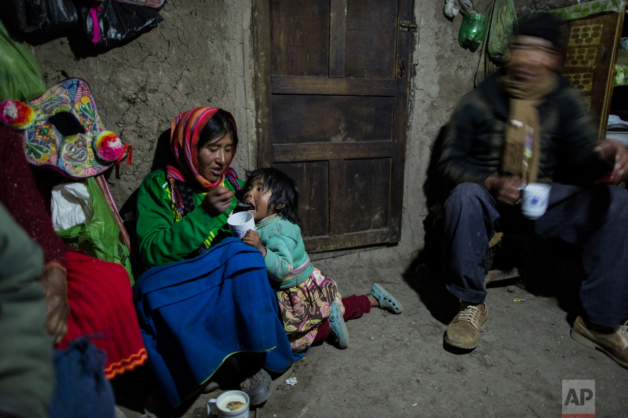 """In this Feb. 4, 2017 photo, Maria Avila feeds her daughter Shomara in their family's adobe home in Coata, a village on the shored of Lake Titicaca in the Puno region of Peru. Avila grew angry as she talked about the lake's contamination. """"My ancestors have lived here more than 500 years. They have never gone through these things,"""" she said. (AP Photo/Rodrigo Abd)"""