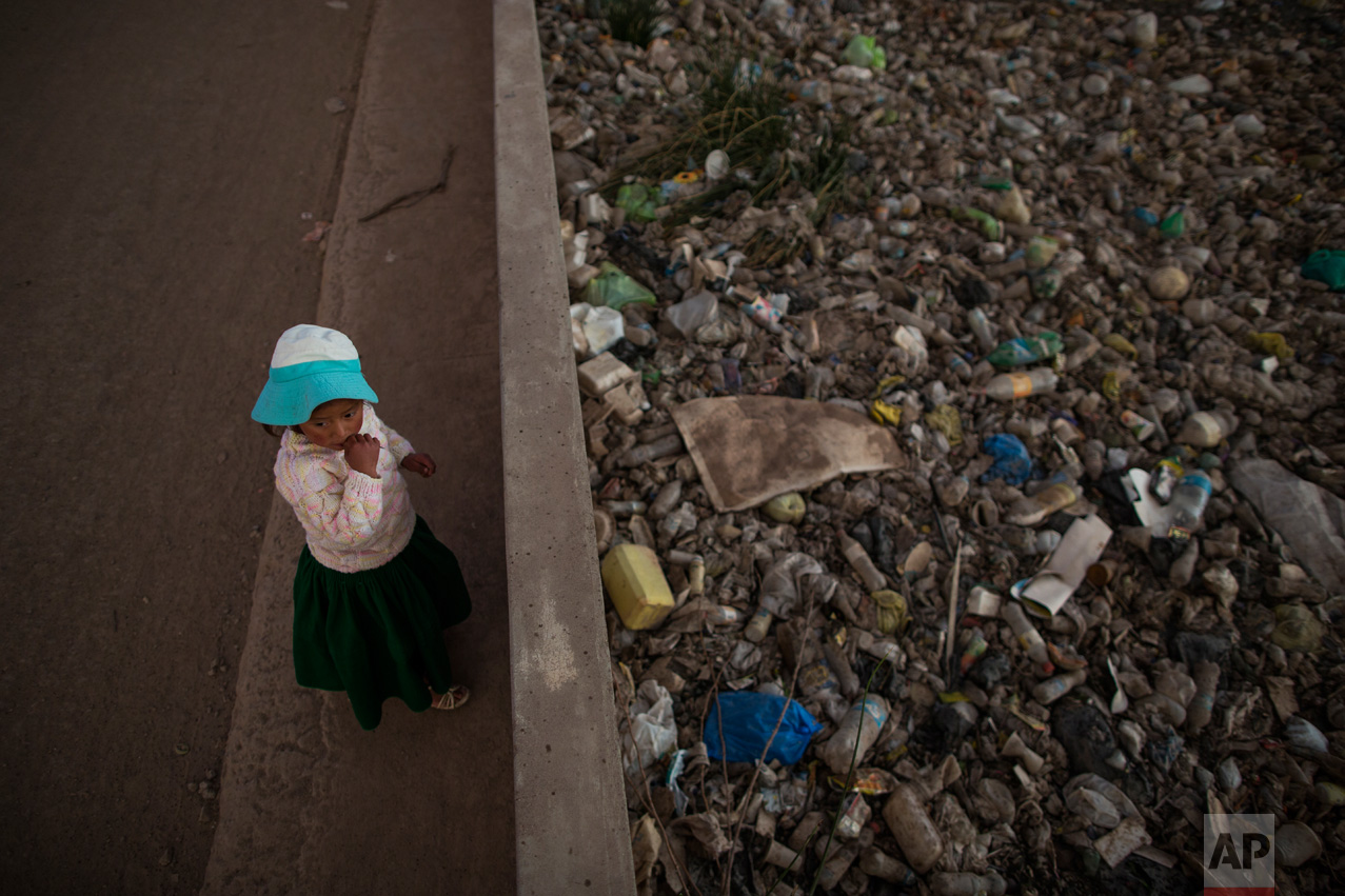 In this Feb. 1, 2017 photo, Maria Jose Campos Inquilla stands next to the trash-filled Torococha River near a municipal waste treatment plant that feeds into Lake Titicaca, in Juliaca, in the Puno region of Peru. In 2011, then-presidential candidate Ollanta Humala promised to resolve the contamination and construct water sewage processing plants. He won 79 percent of votes in the Lake Titicaca region but did not follow through. (AP Photo/Rodrigo Abd)